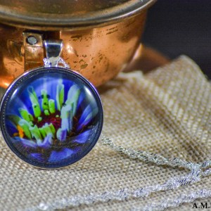 A purple Zinnia flower bloom set in an Shiny Silver bezel with a shiny silver chain. Image captured in the Summer of 2018 and pendant created in the Winter of 2019.