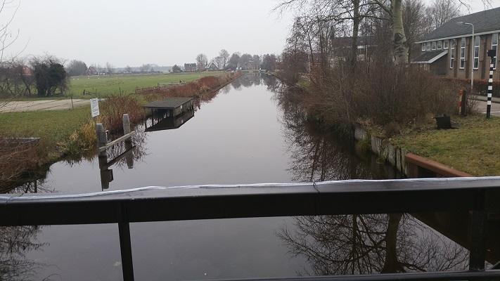 Wandelen over het Groot Frieslandpad op brug over Polderhoofdkanaal in Nij Beets