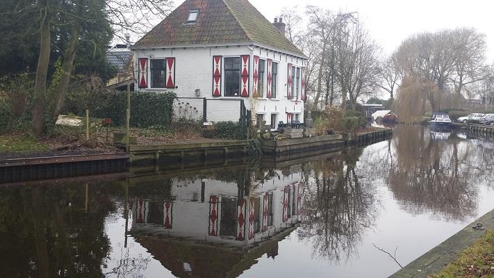Wandelen over het Groot Frieslandpad langs een boerderij aan het Nieuwe Diep in Akkrum