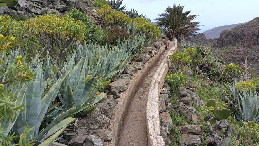 Levada, irrigatiekanaal tijdens wandeling van El Cercado naar La Calera, la Matanza, Wandelpad hoog boven Barranco de Erque tijdens wandeling op een wandelvakantie op La Gomera op de Canarische Eilanden