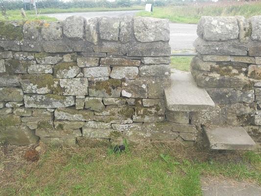 Overstapje over muur op een wandeling van Wallsend naar Heddon on Wall op een wandelreis over de Muur van Hadrianus in Engeland