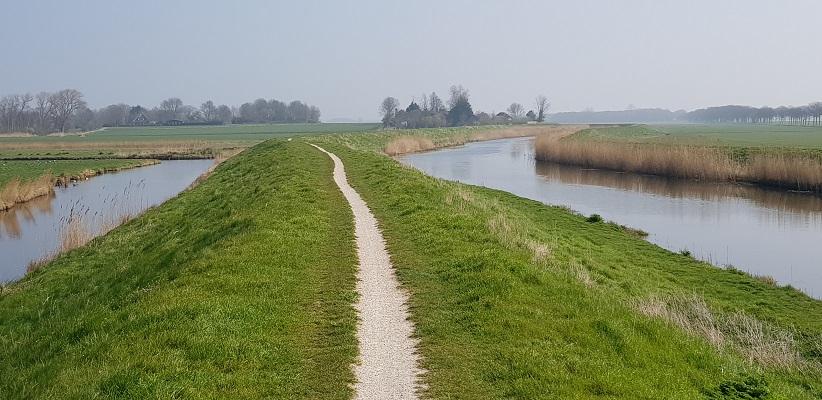 Wandelen over het Noord-Hollandpad van Nieuwesluis naar Den Oever over voetpad op dijk langs Amstelmeerkanaal