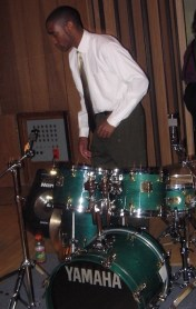 Ambus standing behind a green Yamaha drum set.