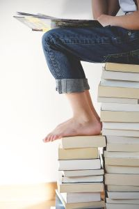 barefoot person sitting on a big pile of books reading
