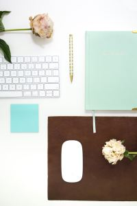 blog desk with pink rose, above a white laptop keyboard sitting next to a teal notebook and post-it, along with a golden pen