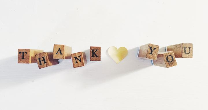 """wooden stamps spell out """"thank you"""" against white background"""