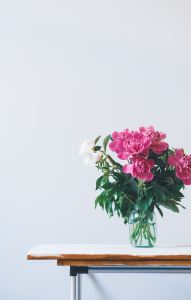 big bouquet of pink and white peonies on white table against white wall