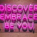 "pink neon sign says, ""discover, embrace, be you."""