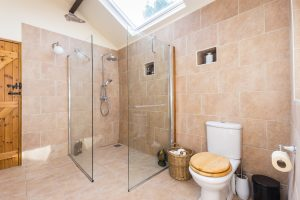 Large wet room with stone effect wall and floor tiles and huge skylight