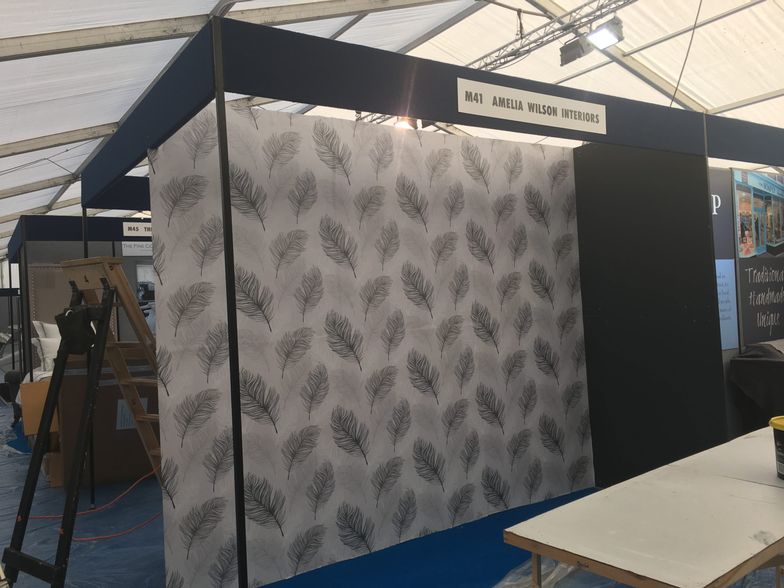 Amelia Wilson Interiors exhibition stand at Lakes Hospitality show. Whisper wallpaper by Arthouse