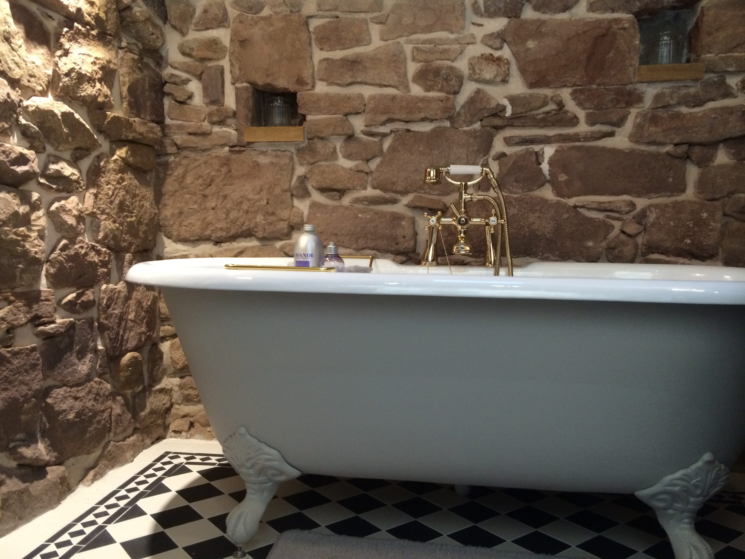 Petite free standing cast iron bath painted in Farrow & Ball Cornforth White in Victorian style bathroom with exposed red sandstone walls