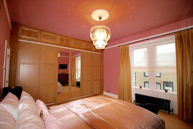 Fitted shaker style wardrobes in pink bedroom designed by Amelia Wilson Interiors Ltd