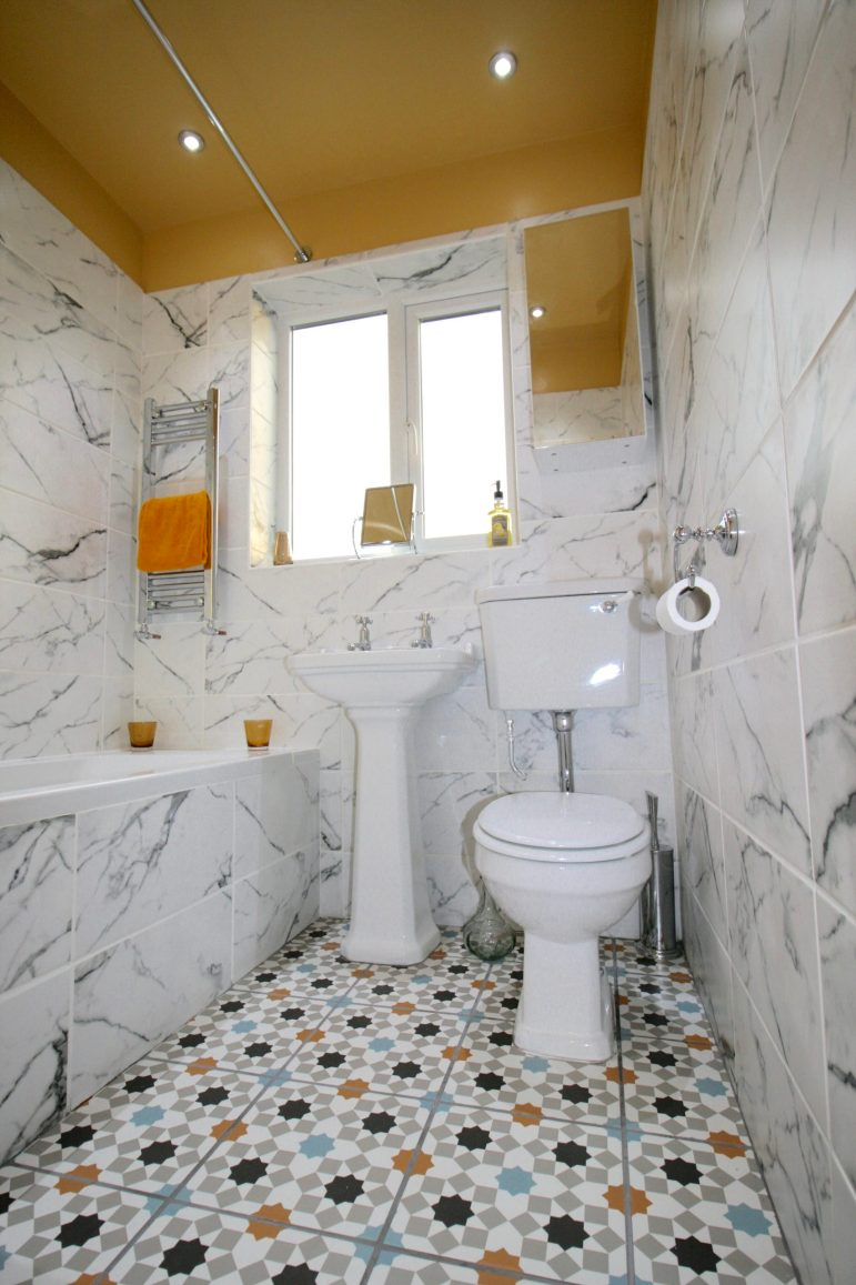 Marble effect wall tiles in small traditional style bathroom with patterned floor tiles