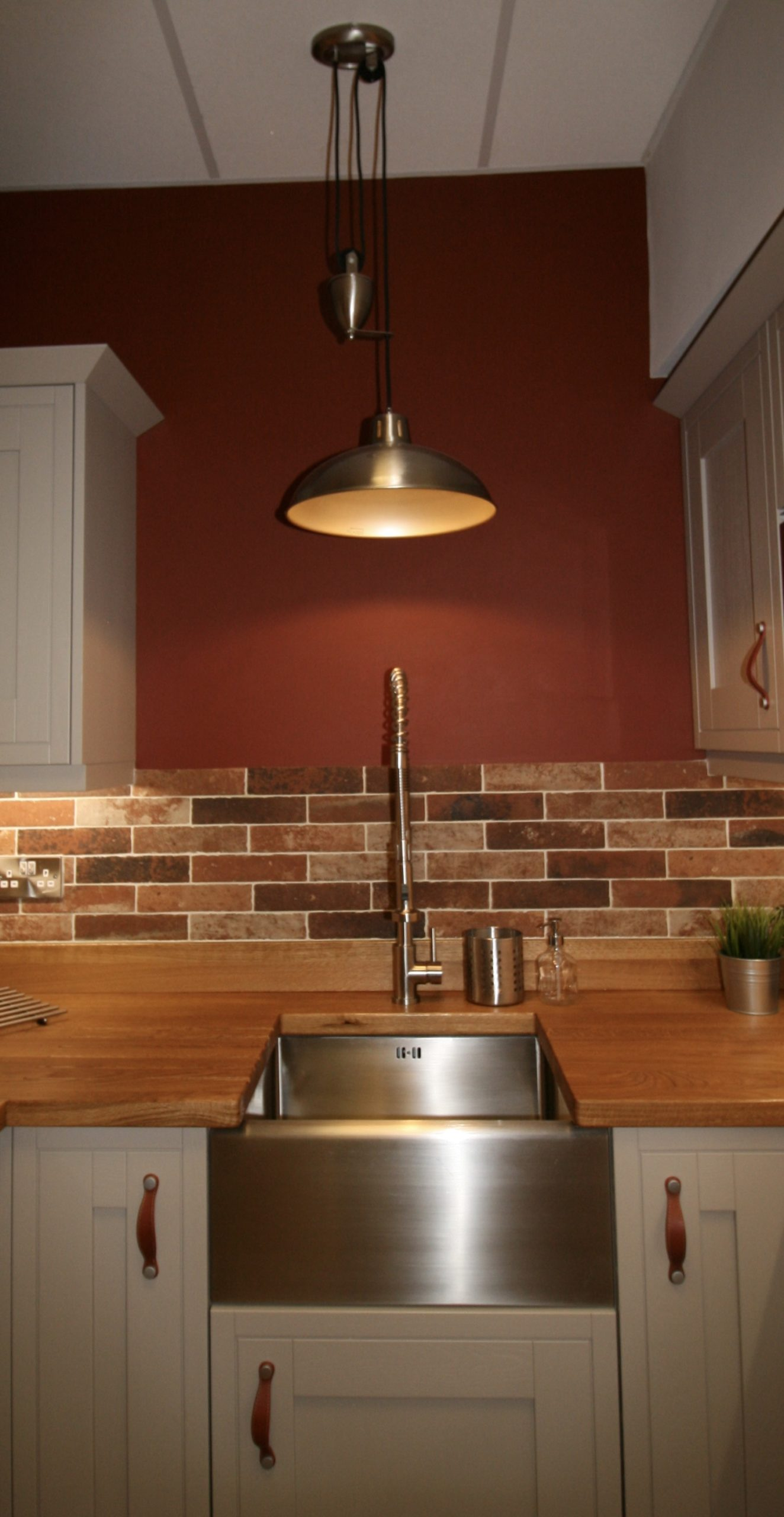 Apron front stainless steel belfast sink with stainless steel rise and fall pendant light. The wall colour is Mince Tarts by Valspar