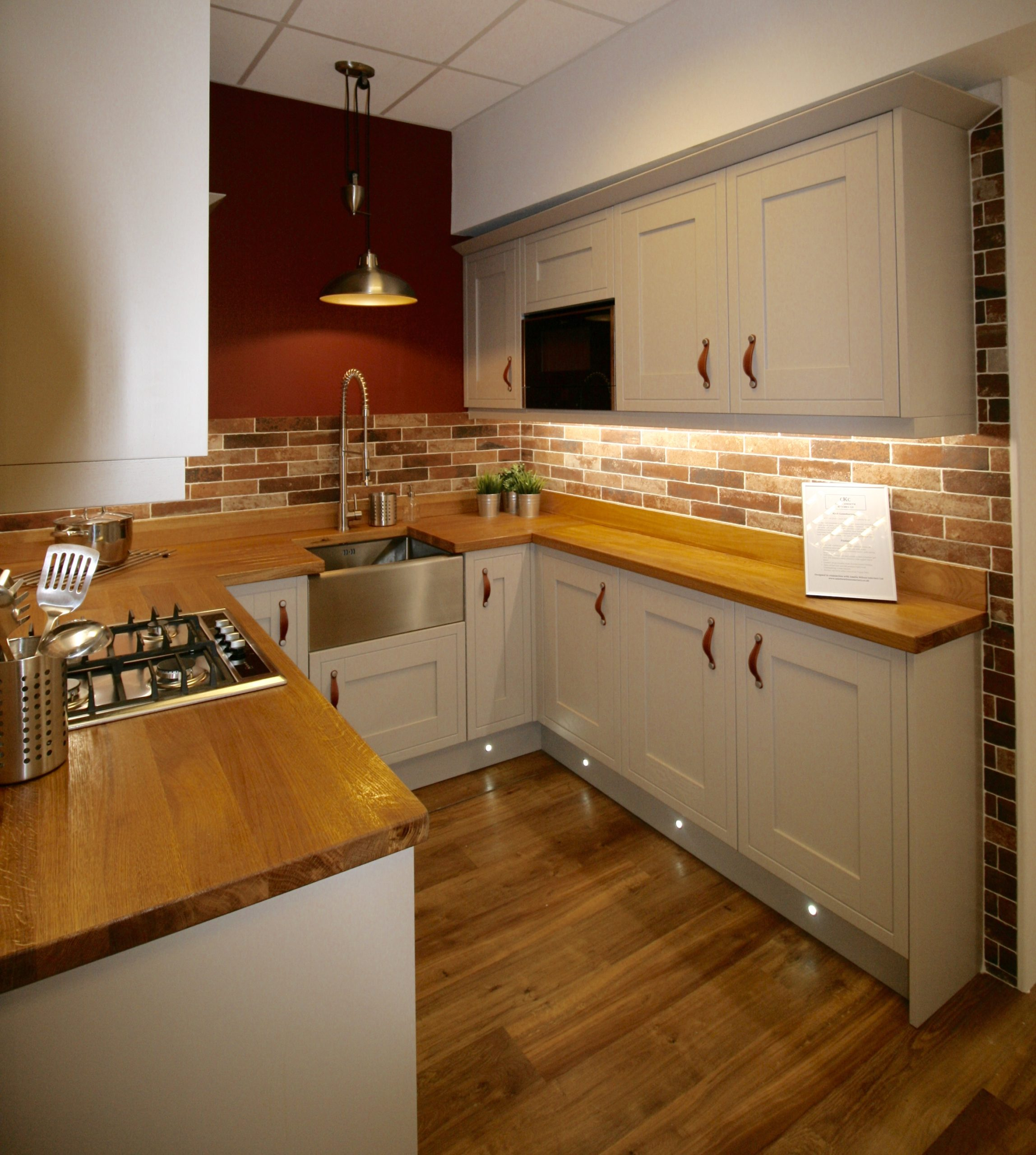 Integrated microwave in the narrow side of the galley kitchen, lit from below by spots in the plinth