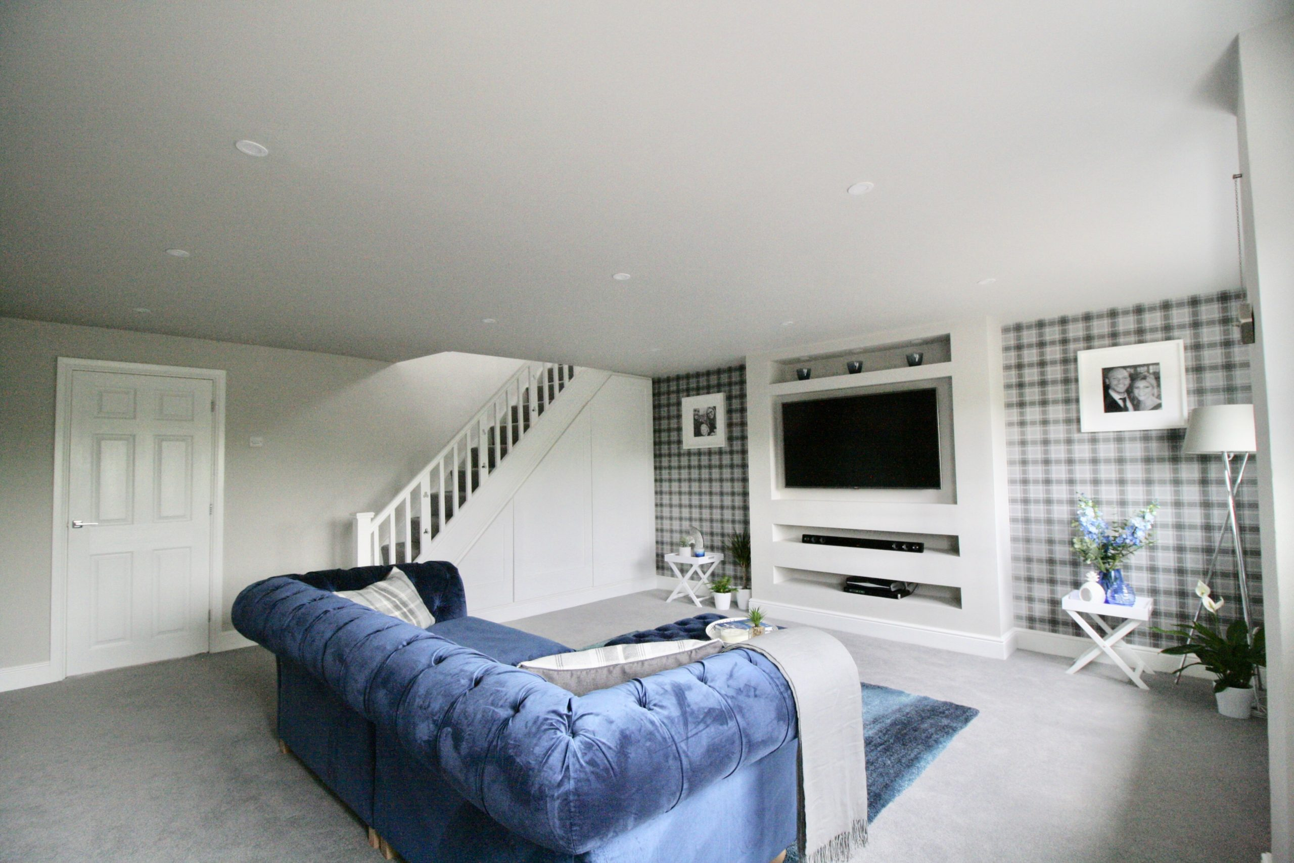 Grey TV room with blue velvet sofa media wall and plaid wallpaper
