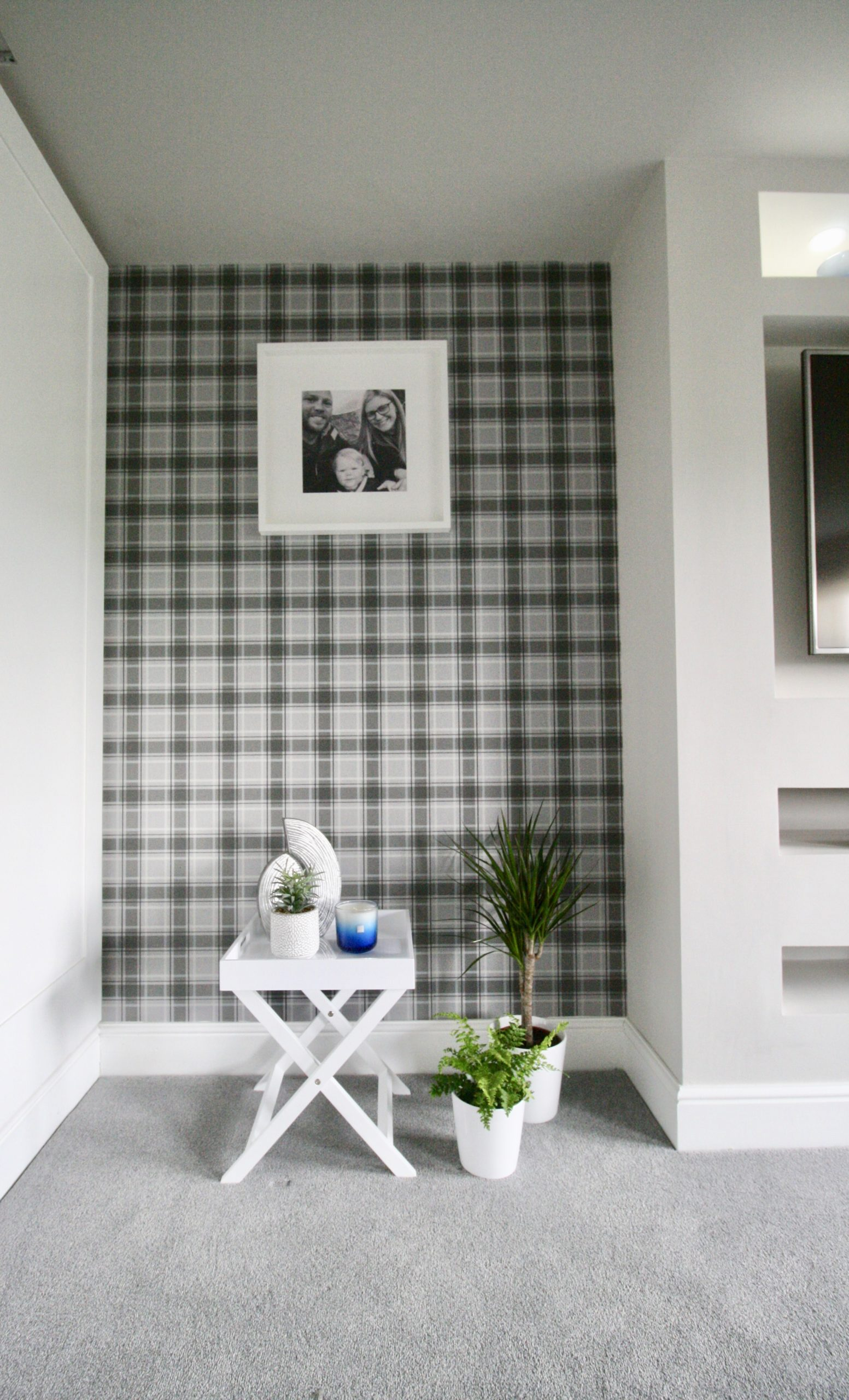Grey tartan wallpaper in TV room with white tray table and white framed artwork