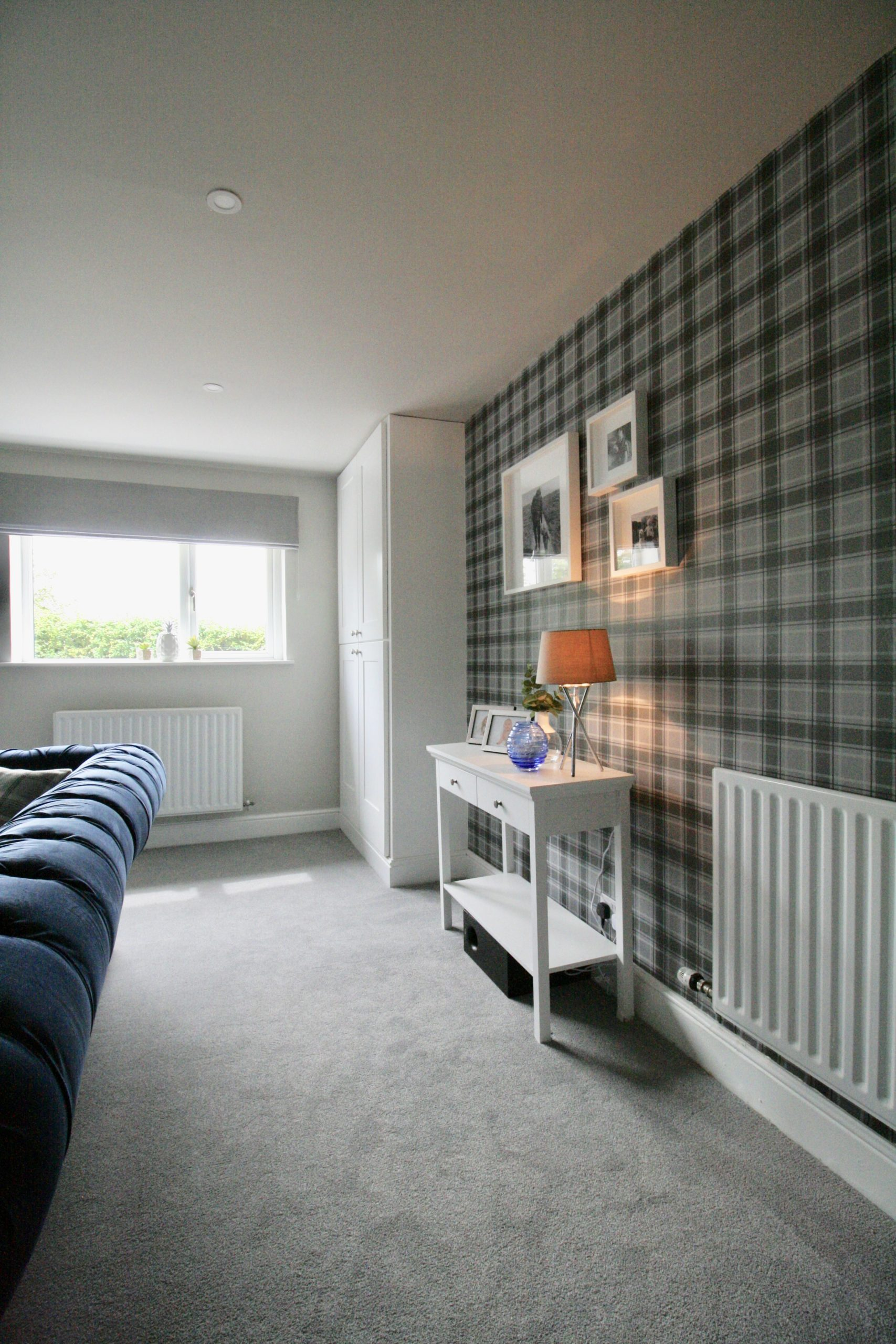 Grey tartan wallpaper white console table white gallery wall in TV room