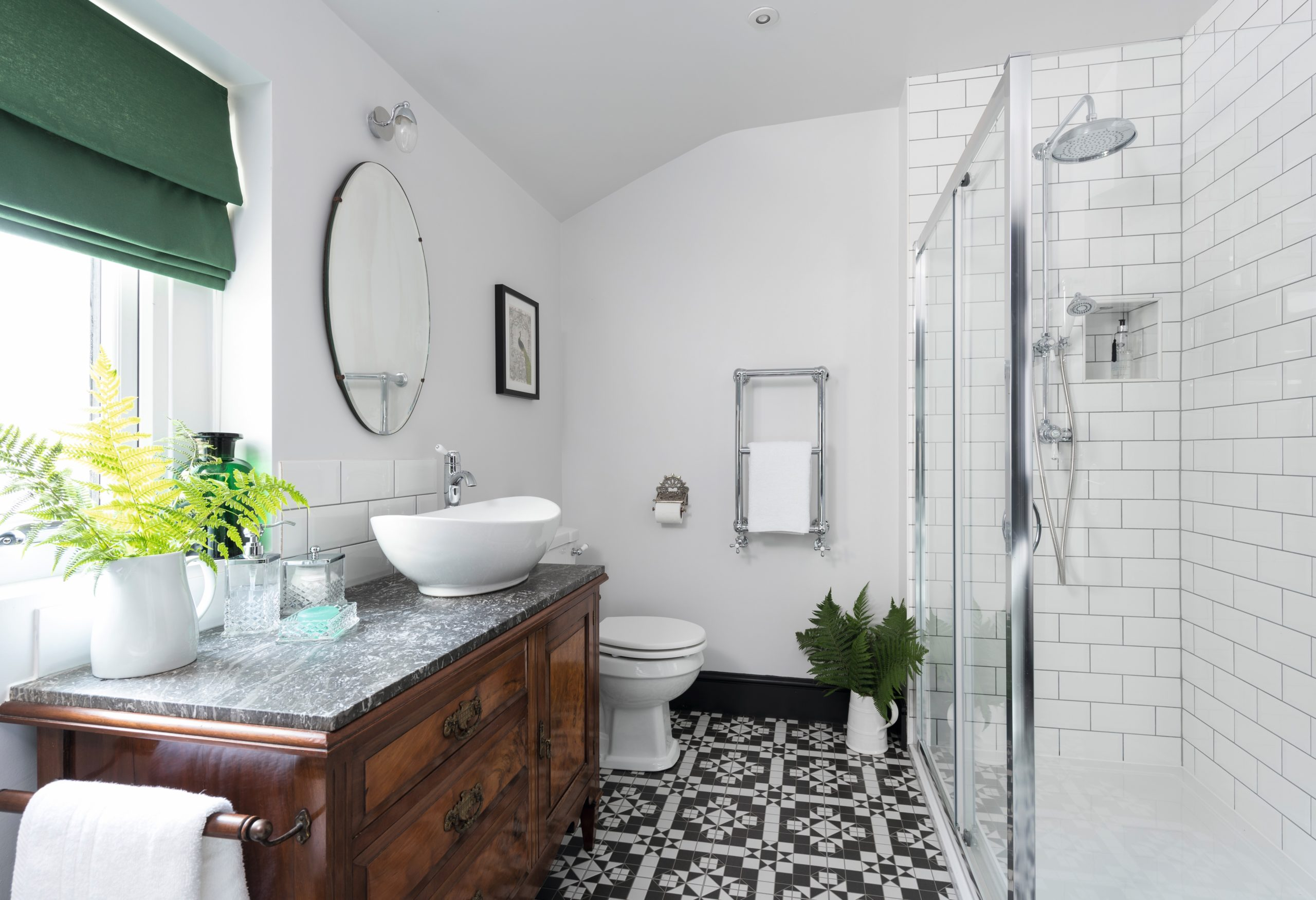 Bathroom with Victorian floor tiles, walk in shower and marble top washstand designed by Amelia Wilson Interiors Ltd