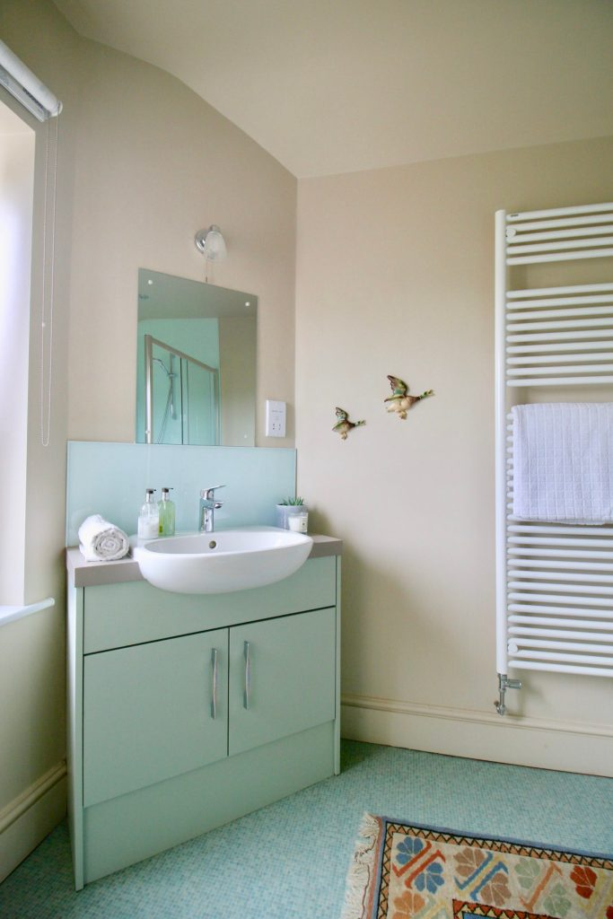 Before and afters. Green vanity unit. White dual fuel towel radiator.