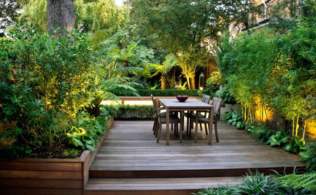 Modern garden with lush planting concealed lighting and decking