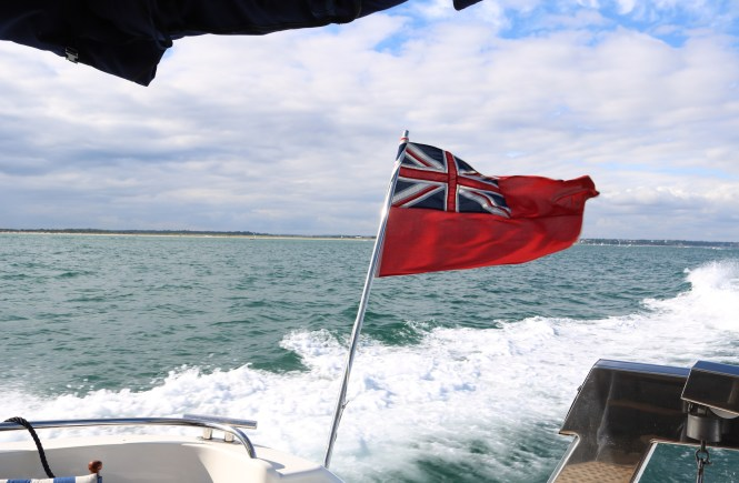 ensign on the back of the boat with the coast line in view