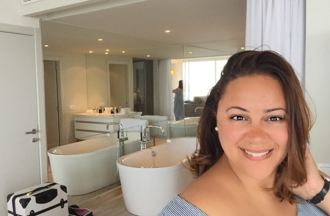 smiling in my suite with the bathtub behind me