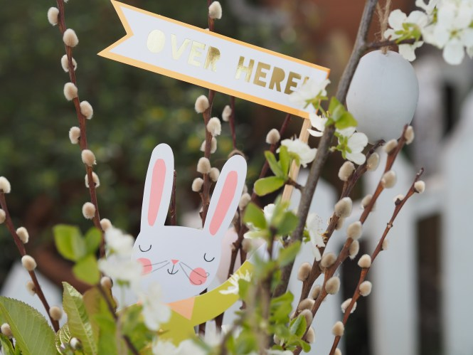"Easter Bunny holding ""over here"" sign"