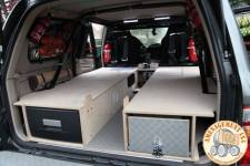 Vue arrière avec les 2 emplacements de couchages (sans les matelas).\nA gauche frigo tiroir 32 litres et à droite tiroir cuisinette avec gaz 2 feux.