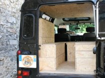 Un meuble haut sur la partie gauche afin d'augmenter l'espace de stockage. Le bas du meuble peut aussi servir de petite table en cas de pluie pour manger à l'intérieur (en s'asseyant en face)