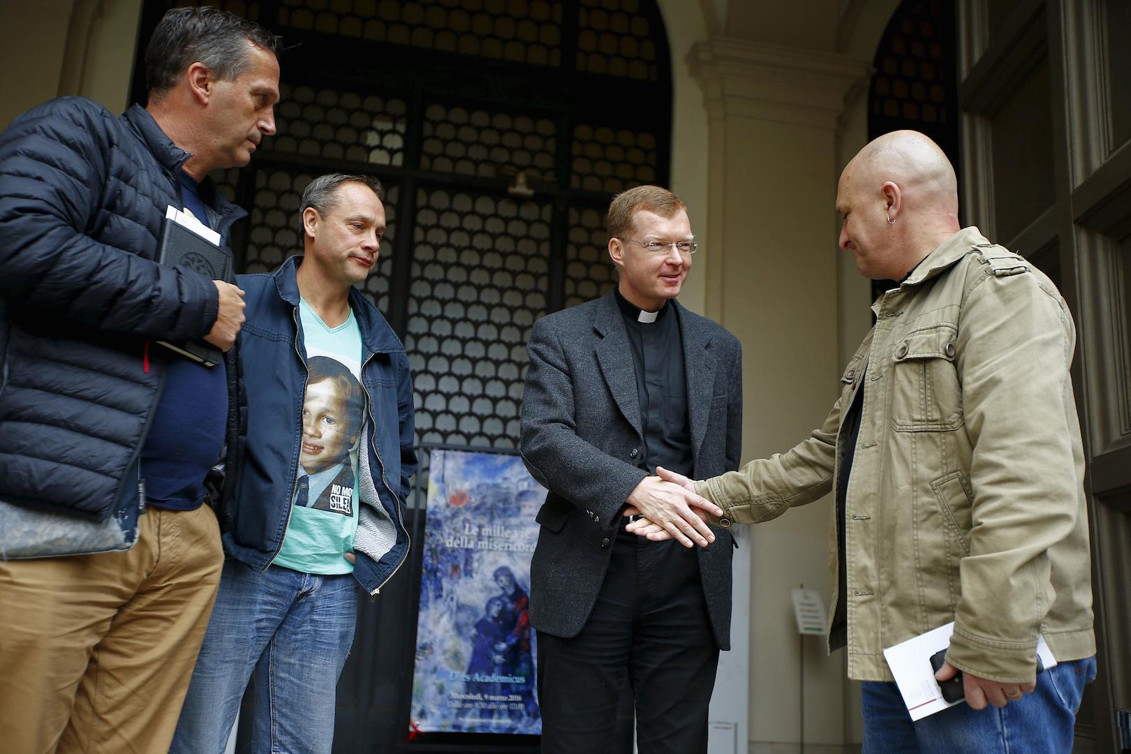 Padre Hans Zollner saluda Andrew Collins, David y Peter Ridsdale Blenkiron en la Pontificia Universidad Gregoriana, 3 de marzo de 2016. Los tres hombres dijeron que fueron víctimas de abuso sexual infantil en Australia.