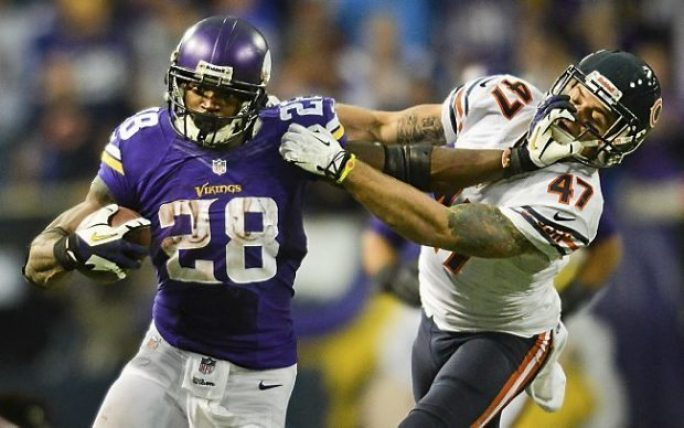 Vikings running back Adrian Peterson takes the ball for 21 yards as he stiff arms Bears free safety Chris Conte in overtime. Peterson ran for 211 yards on 35 carries, and broke the 10,000-yard career rushing mark.   (Pioneer Press: Ben Garvin)