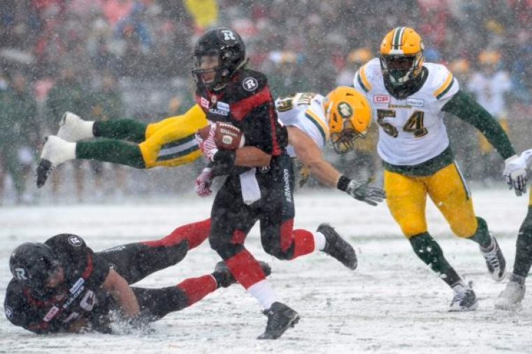 Ottawa RedBlacks' Greg Ellingson (82) makes dodges the Edmonton Eskimos' defenders J.C. Sherritt (47) and Phillip Hunt (54) to deliver a touchdown during first half CFL eastern final action, in Ottawa on Sunday, November 20, 2016. THE CANADIAN PRESS/Adrian Wyld