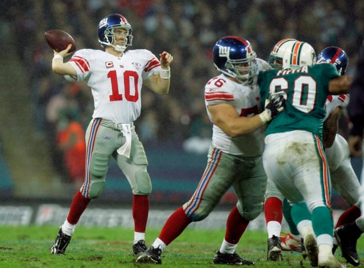 New York Giants' Eli Manning quarter back (10) throws the ball whilst Miami Dolphins, Stiveni Fifita (60 ) is held back during the second quarter of their NFL football game at Wembley Stadium in London, Sunday, Oct. 28, 2007. (AP Photo/Kirsty Wigglesworth)