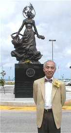 Master Larry Sang at the Guam airport with a Feng Shui statue he recommended after providing a consultation to the airport.