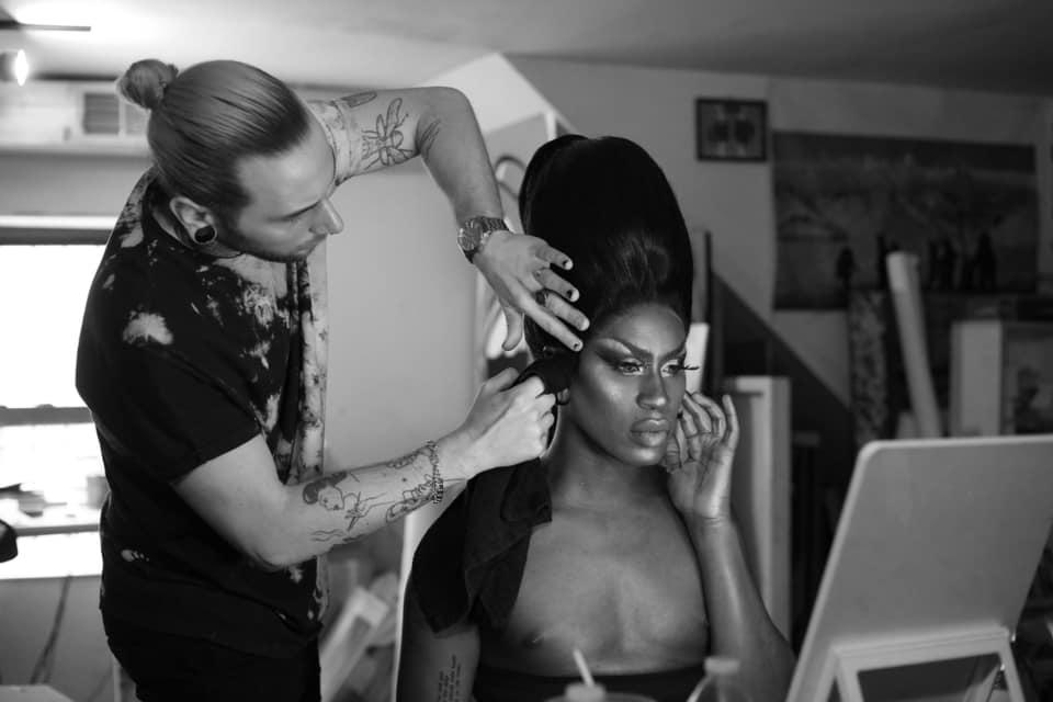 Jordan Phelps fixes the hair of artist Shea Couleé