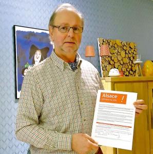 """portrait de Jacques Schleef tenant la pétition """"Alsace retrouve ta voix!"""""""