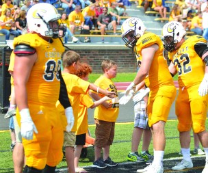 Jeremy Schneider/jeremy.schneider@amnews.com Members of the Centre football team greet the honorees for Saturday's Gold Out Game prior to kickoff at Farris Stadium. The game honored pediatric cancer patients and survivors while also raising money for charity.