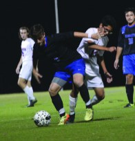 Jeremy Schneider/jeremy.schneider@amnews.com Mercer County's Angelo Ontiveros battles for the ball with Lexington Catholic's Matt Sladic in the first half of the Titans 5-0 win Monday.