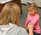 Kendra Peek/kendra.peek@amnews.com Allison King, 5, gets paint applied to her arm by Ella Clay, parent volunteer, at the Junction City Elementary School Fall Festival.