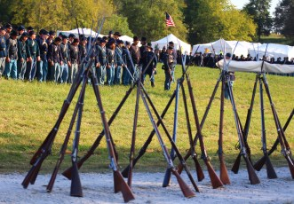 Rifles sit stacked along the side of a road while Union soldier reenactors drill Saturday morning.