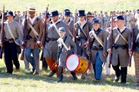 A young drummer marches ahead of a Confederate unit.