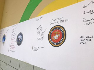 Photo submitted Veterans signed posters at Jennie Rogers Elementary School based on the branch of the military they served.