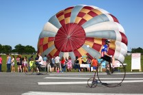 Bikers with the Wheelmen ride antique-style bicycles along the runway as a crowd lines up for tethered balloon rides.