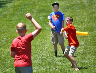 Austin Hagy, right, prepares to swing as he plays baseball with Jack Ferguson, 12, center, and Ben Stretker, 10, left, on the lawn in front of the main stage Saturday. (Photo by Ben Kleppinger)