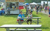 """Kendra Peek/kendra.peek@amnews.com Logan Curtis, 9, left, and Brenden Howell, 9, right, eat and plan before riding the rides at the Boyle County Fair Friday night. Howell, from Oklahoma, was visiting Curtis for the week, the """"perfect"""" week, Curtis said."""