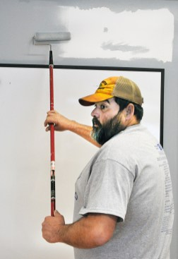 Shawn Davis paints a wall in the art room at the Community Arts Center.