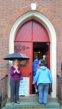 Mimi Becker greets MLK marchers outside the front door of Trinity Episcopal Church. (Photo by Robin Hart)
