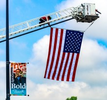 Danville Firefighter Stephen Glovak secures a giant U.S. flag to the top of Danville's ladder truck prior to the start of Saturday's Great American Brass Band Festival Parade.