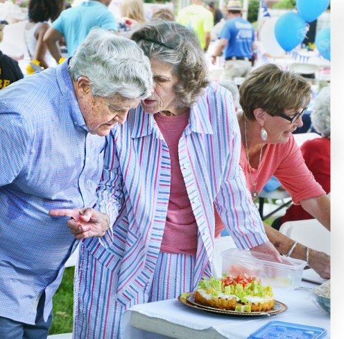 Caroline Hogwood talks with Buz Creekmore as they get their picnic offerings ready Saturday evening.